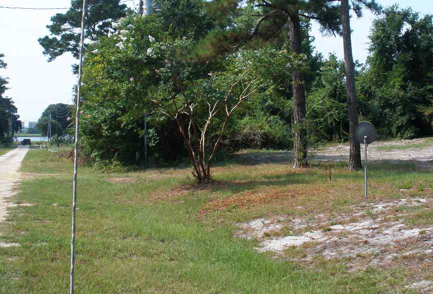 This picture shows the corner of lot 11. It is the iron post just beyond the neighbors satellite dish. It also shows the road going down along the rest of the lots. .